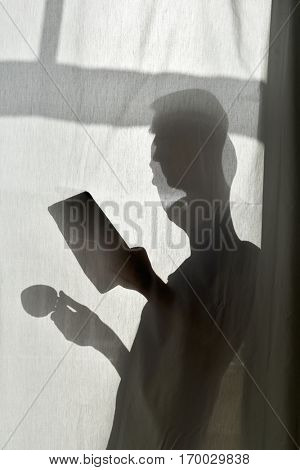 the silhouette of a young man behind a white curtain with a cup of coffee or tea in one hand and a tablet in the other hand