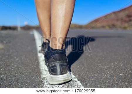 closeup of the feet and legs of a young caucasian man seen from behind walking by the center line of a road