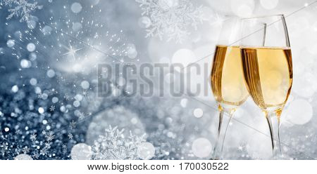 Glasses with champagne against fireworks and sparkling holiday lights
