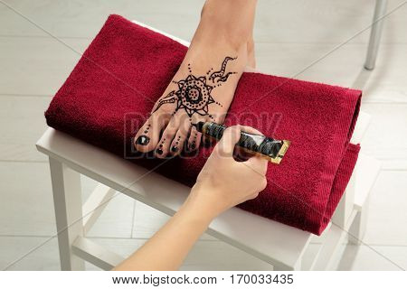 Woman applying henna on female foot