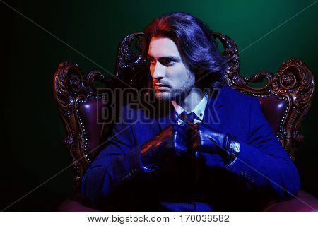 Handsome man in an expensive suit and black leather gloves sitting in a classical vintage armchair. Male beauty, fashion. Accessories.