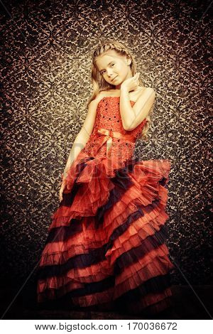 Fashion concept. Pretty eight year old girl in beautiful long evening dress posing over vintage wallpaper. Kid's fashion.