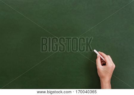 Teacher or student hand holding a chalk stick about to write on a blank green chalkboard with copyspace