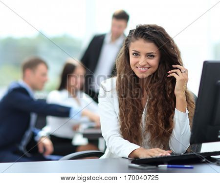 beautiful girl assistant in the office in front of a computer in