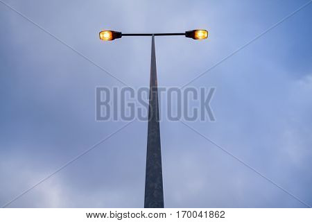 Lit modern streetlamp at evening or early night with an orange bulb and sky with clouds