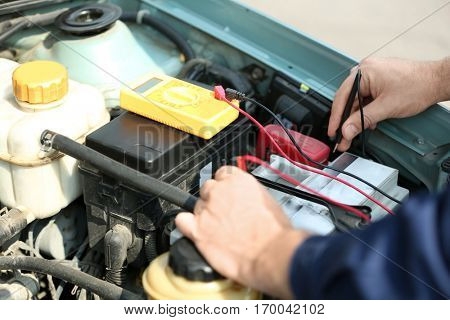 Mechanic hands with scan tool diagnosing car in open hood. Closeup