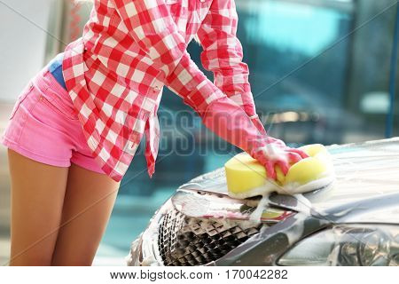 Woman washing car with sponge
