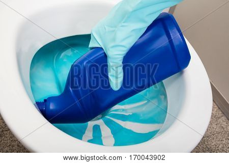 Close-up Of A Person's Hand Wearing Gloves Cleaning Toilet Using Detergent Bottle