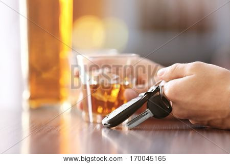 Man sitting in bar with alcoholic beverage and car key, closeup. Don't drink and drive concept