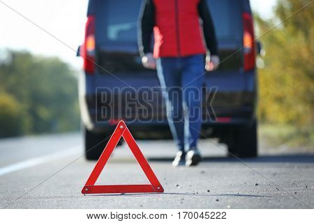 Red warning triangle on asphalt road. Driver near broken down car