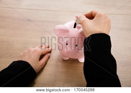 Close-up Of A Businesswoman Inserting Coin In A Piggy Bank On Wooden Desk. Money Saving Concept