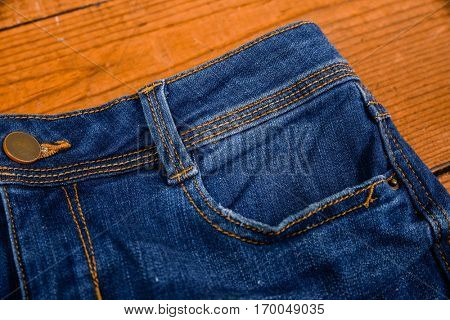 Blue jeans detail with pocket- board background