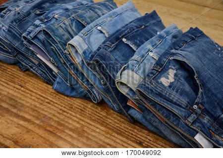 Pile of jeans trouser on wooden background