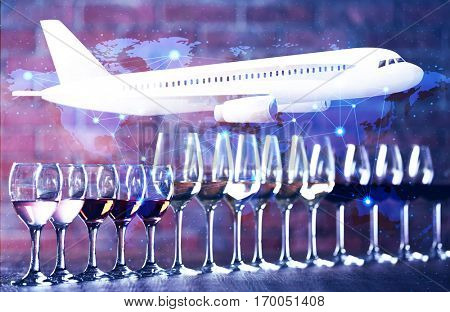 Glasses of different wine on table. Airplane and world map on background