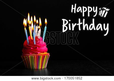 Cupcake with candles and text HAPPY BIRTHDAY on black background