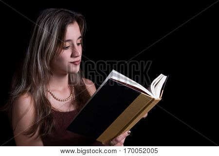 Beautiful hispanic teenage girl reading a book isolated on a black background