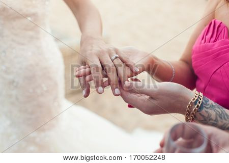 Bride shows wedding ring to girlfriend close-up