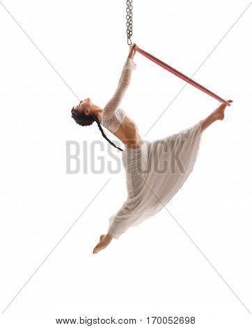 Side view of graceful aerial acrobat doing acrobatic tricks with ring.  Young flexible aerialist performing with hoop on white isolated studio background