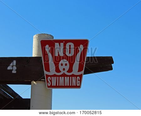 Red no swimming sign with white lettering and an illustration showing a swimmer drowning against a clear blue sky.