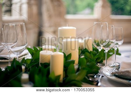 Candles and goblets on a decorated wedding table close-up