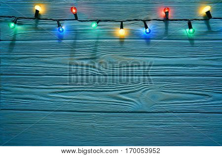 Christmas dark blue wooden background decorated with shining lights