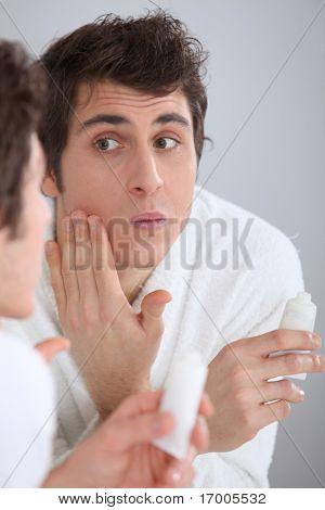 Portrait of man applying moisturizer on his face
