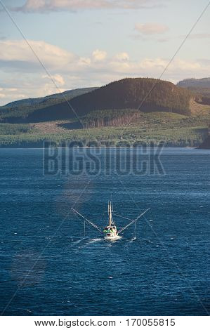 Fishing trawler at sea in blue water. Sea food vessel carry shrimps