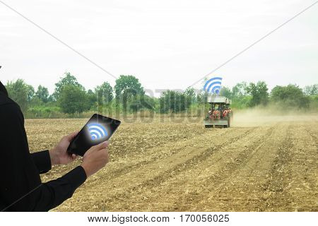 iot internet of things industrial agriculture concept smart farming. Farmer use wireless application to control and receive the data between mobile phone and truck or machine in the farm or field