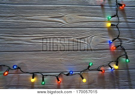 Christmas dark  wooden background decorated with shining lights border frame