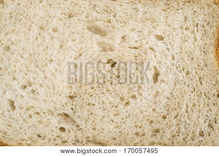 Slice of Bread on an Old Cutting Board Background. Porous and Wooden Texture Closeup