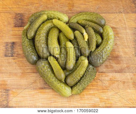 Homemade Pickled Gherkins in the Shape of a Heart. Marinated Cucumbers Over Rustic Wooden Background