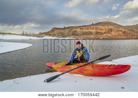 winter kayaking in Colorado - senior male with red whitewater kayak on shore of Horsetooth Reservoir near Fort Collins