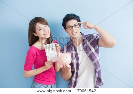 young couple hold pink pig bank and calculator isolated on blue background