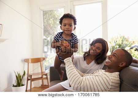 Parents And Son Playing Game On Sofa At Home