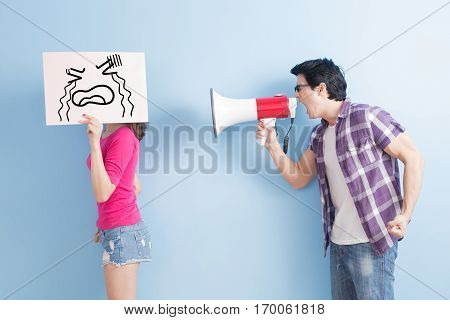 man take the microphone shout to woman angrily isolated on blue background