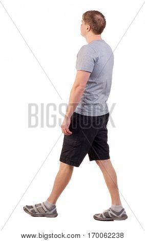 Back view of walking handsome man in shorts and sneakers.   Sports-dressed young man moves. backside view of person.  Isolated over white background. sportsman in summer clothes are left