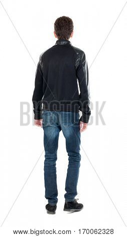Back view of handsome man in winter jacket  looking up.   Standing young guy in parka. Rear view people collection. Isolated over white background. A guy in a black jacket standing and looking forward