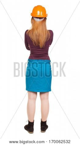 Backview of an woman engineer in construction helmet stands. Standing young woman.  backside view of person.  Isolated over white background.  Young girl crossed her arms over her chest and watches