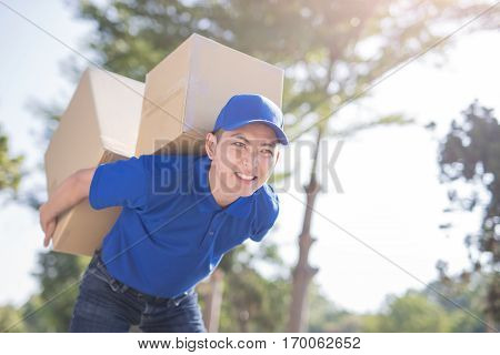 deliveryman hold heavy box and smile asian