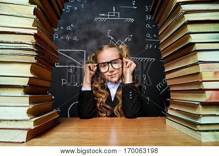 Portrait of a smart schoolgirl in glasses posing with books over school blackboard. Educational concept.