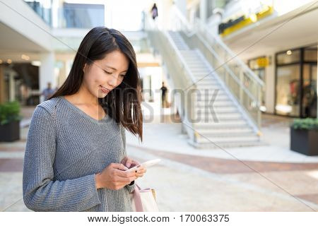 Asian woman using mobile phone in shopping center