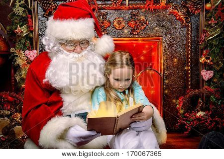 Good old Santa Claus and a small girl reading fairy tales. Beautiful room with Christmas tree and fireplace decorated for Christmas.