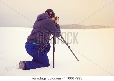 A traveler on the background of winter landscape.Young photographer smitrit forward on the banks of the dam.  It surrounds winter nature.