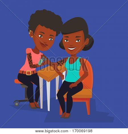 An african-american female tattooist makes a tattoo on the hand of a woman. Tattooist makes a tattoo to a client. Professional tattoo artist at work. Vector flat design illustration. Square layout.