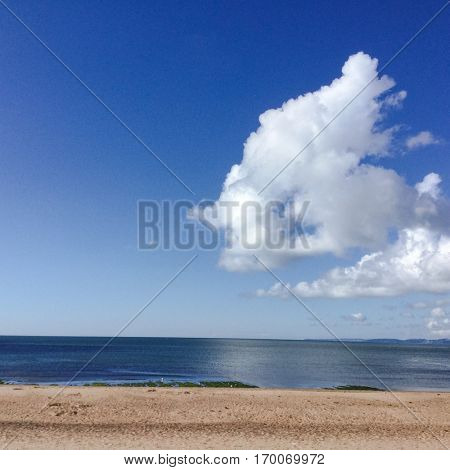 Sea, sand and sky with cumulus clouds  on a sunny day.