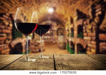 Small and old wine cellar with two glasses of red wine, served on wooden planks