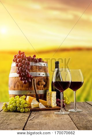 Red wine glasses with bottle served on wooden planks with keg, vineyard on background, copyspace for text