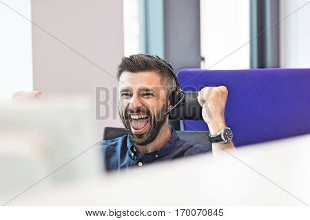 Successful mid adult businessman wearing headset while clenching fists in office