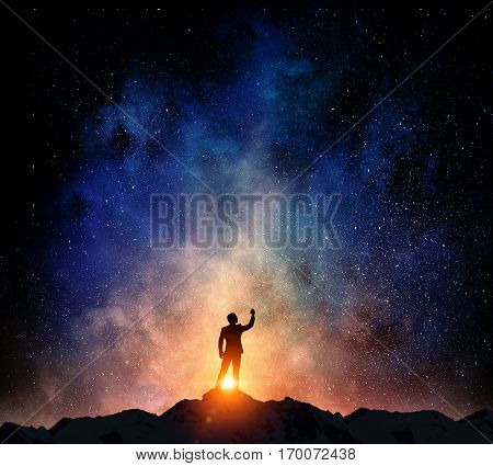 Businessman against starry sky . Mixed media