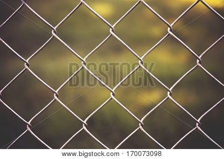 a nice chain link fence in front of green grass in a park or yard on a summer day with a vignette around the border good for background use toned with a retro vintage instagram filter effect app
